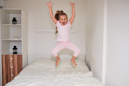 Laughing little girl jumping on big white bed, having fun on weekend morning in bedroom