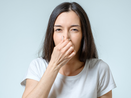 Photo pour Girl covers nose with hand showing that something stinks isolated on gray background - image libre de droit