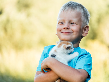 Little boy at countryside holding his lovely fluffy kitty cat. Pets and lifestyle concept