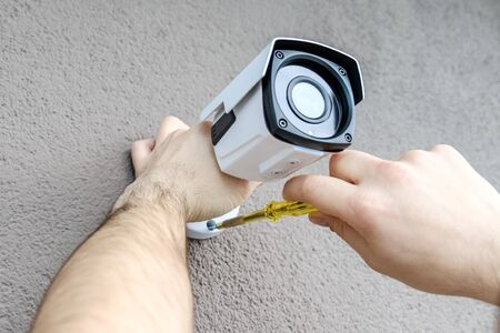 Photo for Technician worker installing video surveillance camera. CCTV camera closeup - Royalty Free Image