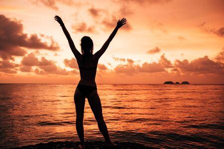 Foto für Lady's silhouette with raised arms against calm sunset beach - Lizenzfreies Bild
