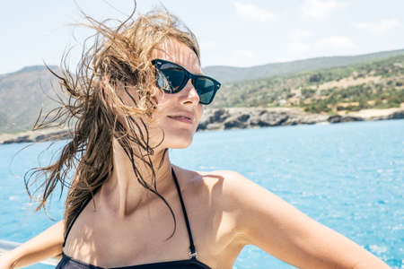 Photo for Happy female tourist having fun on sailboat. Summertime sailing vacation. Beautiful woman outdoor in bikini - Royalty Free Image