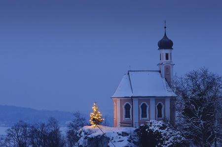 christmas chapel and illuminated tree at eve night in upper bavaria, germany
