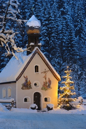 christmas chapel at evening with illuminated tree