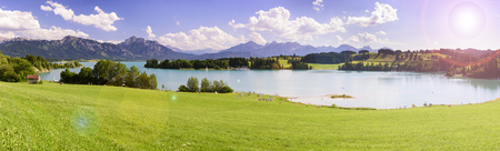panoramic landscape in Bavaria with alps mountain range and lake Forggensee