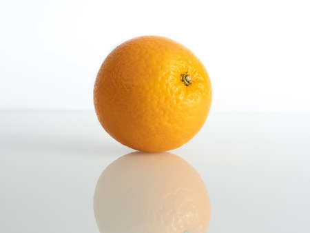 Photo for an orange inch on a white background in reflection of the base - Royalty Free Image