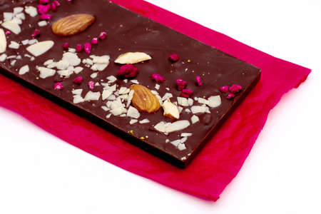 Photo pour Handmade white, milk and dark chocolate bar with a variety of dried fruit and nut toppings on a red paper over white background - image libre de droit