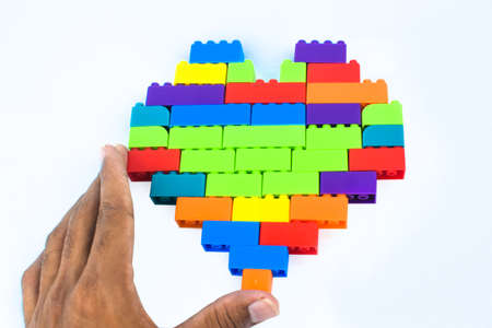 A person making a heart shape with lot of different colored building blocks in front of a n isolated white background