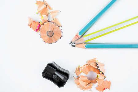 Foto de Study materials containing black color pencil sharpener and three wood pencil crayons - Imagen libre de derechos