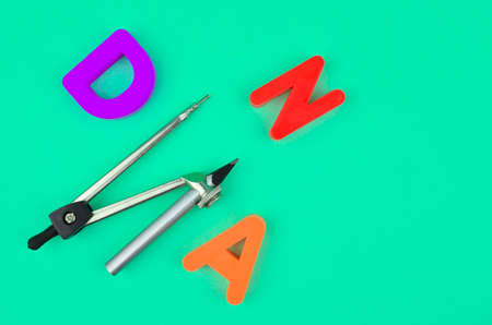 D N and A letters and a silver compass attached to a pencil placed on a blue paper background