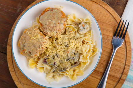 Photo pour Pasta in a creamy sauce with mushrooms and chicken meatballs in a beige plate on a wooden table Horizontal photo. - image libre de droit