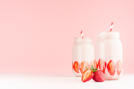 Photo for Spring healthy milk beverages with cut ripe strawberry, red striped straws on gentle pastel pink background, white wood table, copy space. - Royalty Free Image