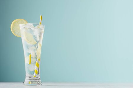 Photo for Homemade diet transparent lemonade with lemon, ice cubes, soda, yellow striped straw in misted glass on white wood table, pastel green color background. - Royalty Free Image