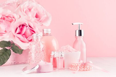 Photo pour Different skin care products with romantic roses bouquet on girlish elegant pink pastel background with copy space. - image libre de droit