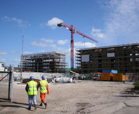construction workers walking near building site with crane