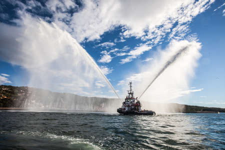 Inauguration of the Worlds Offshore Sailing, tugboat shooting water in the sunset.Muggia, Trieste, Italia.
