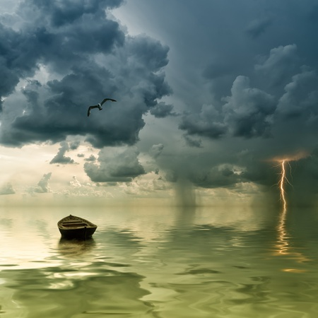 The lonely old boat at the ocean, comes nearer a thunder-storm with rain and lightning on background
