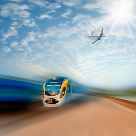 High-speed commuter train and airplane with motion blur, majestic clouds and sun