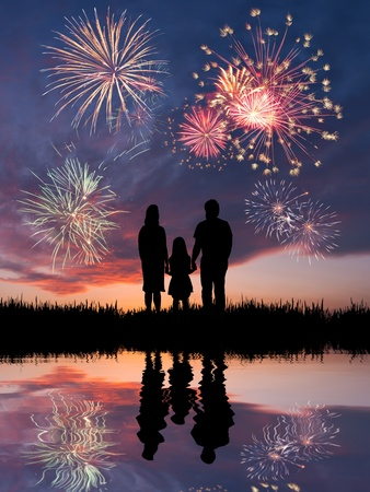 The happy family looks beautiful colorful holiday fireworks in the evening sky with majestic clouds