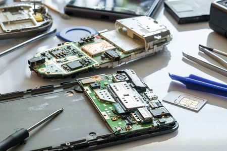 Cell phone repair. Smartphone parts and tools for recovery, selective focus