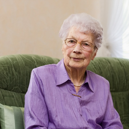 Photo for 91 years old woman sitting on couch in her living room, portrait - Royalty Free Image