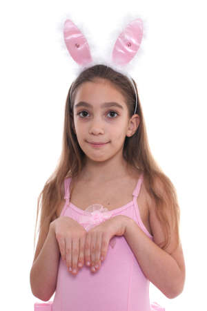 Portrait of girl wearing ballerina outfit and rabbit ears looking at camera isolated on white background