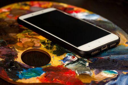 Photo pour the mobile phone lies on the artist's palette with oil paint - image libre de droit