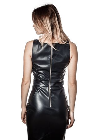 Photo pour a girl in a black leather dress turned her back on a white background - image libre de droit
