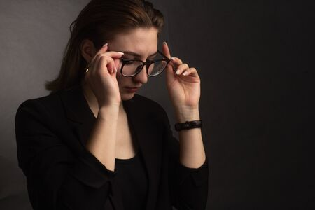 Photo pour Portrait in the photo Studio of a brown-haired girl, on a black background in a black business jacket. Short hair. jabs at his glasses with two hands - image libre de droit