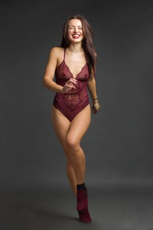 Photo pour a brunette girl in a Burgundy bodysuit poses and dances on a gray Studio background - image libre de droit
