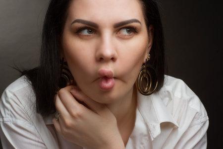 Photo pour Studio portrait of a brunette in a white T-shirt she purses her lips, making duck lips - image libre de droit