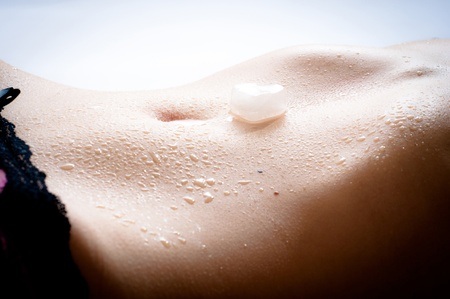 Wet female flat tummy with a slice of ice in the form of heart