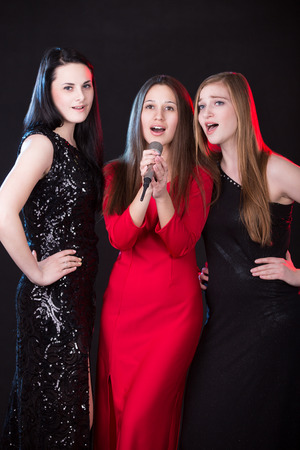 Group of three elegant beautiful young women vocalists with microphone singing