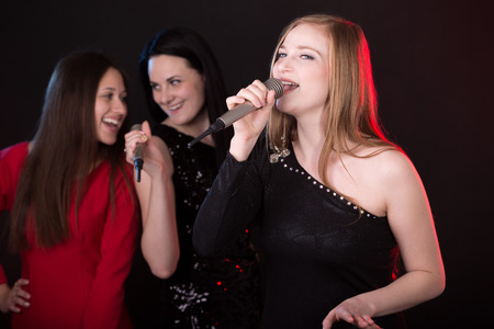 Portrait of beautiful emotional female singer with microphone singing with passion, back vocalists on the background