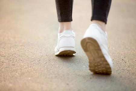Photo pour Female feet in white sneakers running on concrete, jogger practicing, close-up. Healthy, active lifestyle concepts, copy space - image libre de droit