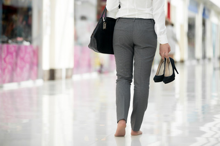 Young woman in office style clothes carrying in hand her high heel shoes, walking barefoot in contemporary building, legs close-up