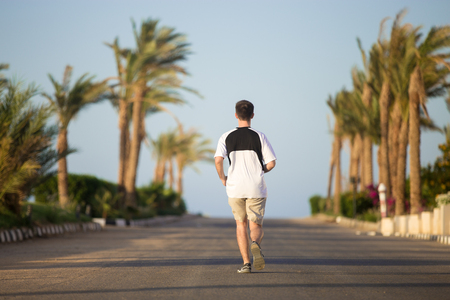 Sporty young man running away from camera, doing jogging practice on the sunny summer street in tropics, palm trees on the background, full length, back view
