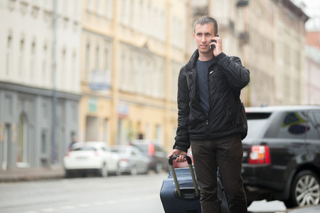 Young smiling handsome man with luggage bag walking on rainy city street with busy traffic holding cellphone, making call, talking on mobile phone, travelling, wearing casual clothes