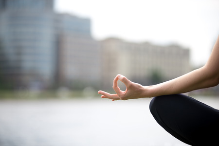 Close up of hands of young office yogi woman sitting cross legged in yoga Easy Sukhasana Pose on riverbank in the city, meditating with fingers in Jnana mudra