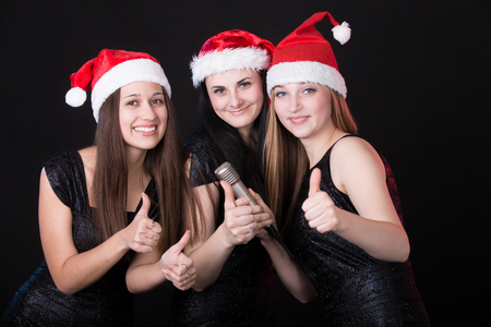 Group of three positive, happy smiling beautiful girls vocalists posing in cute red santa claus hats with microphone, showing thumbs up, black background