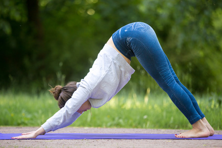 Profile of beautiful sporty young woman working out on street, doing stretching exercises on blue mat in park alley, standing in downward facing dog pose, surya namaskar, full length