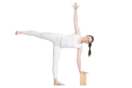 Sporty beautiful young cheerful female beginning yoga student in white sportswear standing in ardha chandrasana (Half Moon Pose) leaning on wooden block, studio full length isolated shot