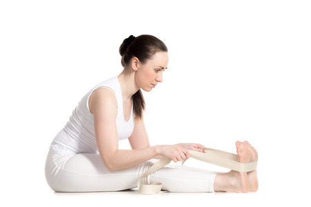 Sporty beautiful young woman doing warming up stretching exercises, sitting in seated forward bend pose, doing easy paschimotanasana variation with strap, studio full length isolated shot
