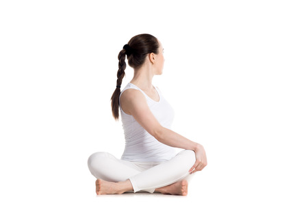 Sporty beautiful young woman in white sportswear practicing yoga, sitting cross legged in Revolved easy pose, spinal twist, parivrtta sukhasana, studio full length isolated shot, front view