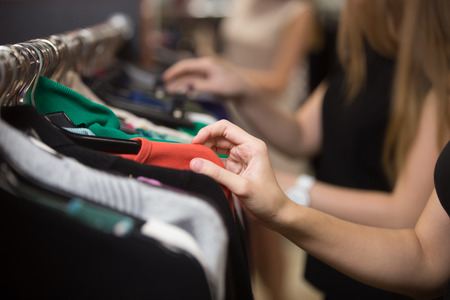 Foto de Young beautiful women shopping in fashion mall, choosing new clothes, looking through hangers with different casual colorful garments on hangers, close up of hands - Imagen libre de derechos