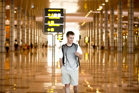 Smiling young man with backpack in his 20s walking in modern airport terminal building, holding smartphone, looking at screen, using cell phone app, typing or reading text message