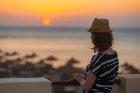 Young woman in hat and cute summer dress standing at the terrace with peaceful sea scenery, looking at sunset or sunrise on horizon, back view, copy space