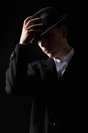 Handsome unrecognizable elegant mafioso man in coat touching his hat as in greeting, scarcely visible in the darkness