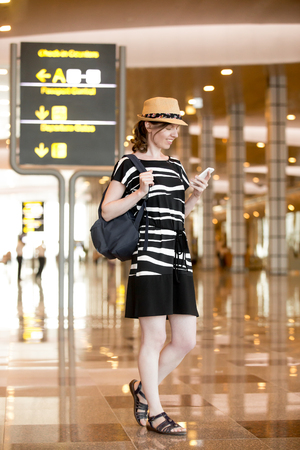 Smiling young woman in straw hat waiting for flight, standing in public Wi-Fi area in modern airport terminal, holding mobile phone, looking at screen, using smartphone app, messaging, full length