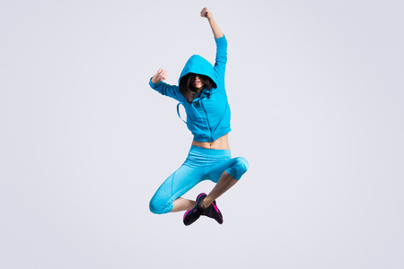 Foto de One beautiful young fit modern dancer lady in blue sportswear hoodie sweater working out, dancing and jumping, full length, studio image on gray background - Imagen libre de derechos
